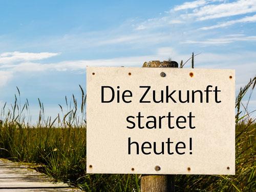 """Bild von einem Steg am Strand mit grünen hohen Gräsern an der Seite. Vorne im Bild steht ein Schild mit der Aufschrift """"Die Zukunft startet heute!"""""""