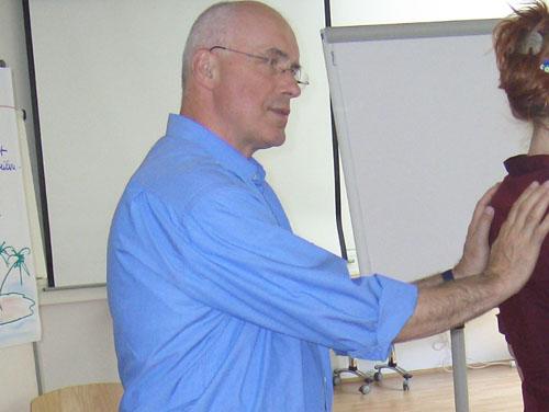 Vortragender legt Hände auf den oberen Rücken (Schulterblätter) einer Teilnehmerin und erklärt Ablauf einer Übung.
