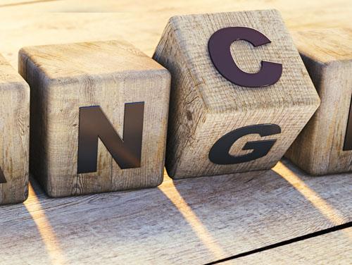 """Symbolbild: Holzwürfel mit den Buchstaben NG darauf für """"Change"""" (Veränderung)."""